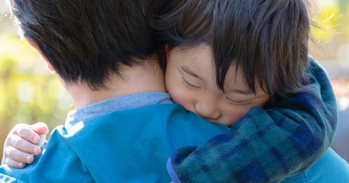 young child hugging adult