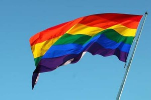Photo of a Rainbow Flag flying in the wind, a symbol of the equal rights movement for the LGBTQIA community.