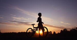 Silhouette of child biking independently