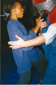 Woman kicking a padded instructor