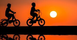 Silhouette of two kids riding bikes during sunset