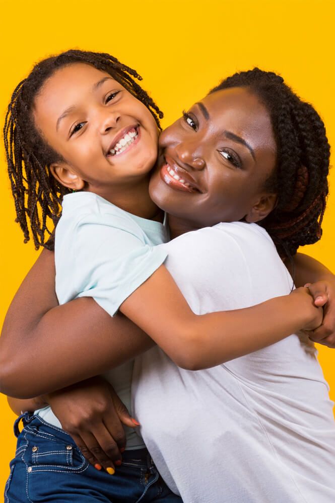 woman with braids and child hugging and smiling