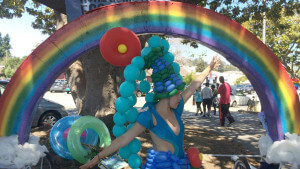 Large rainbow made of balloons with colorful balloon-decorated dancer
