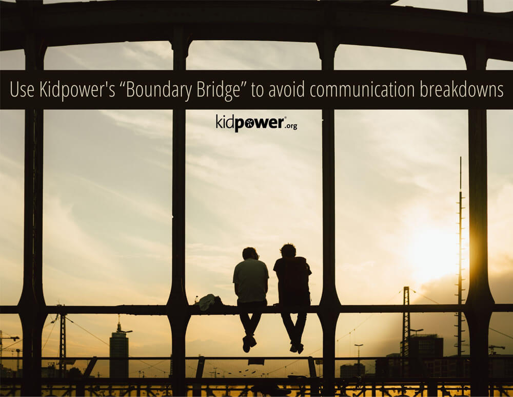 Two people sitting on a bridge and talking.