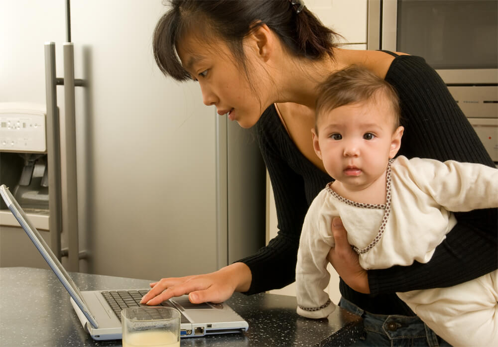 An adult multitasking holding a baby and looking at laptop