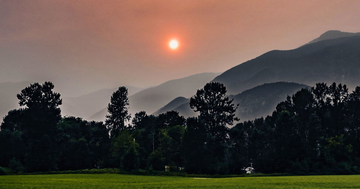 Scene of smokey sky and red sun