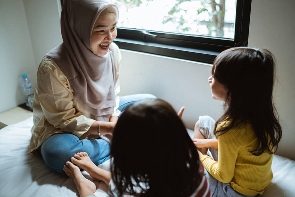 Woman in hijab sitting and teaching two young girls