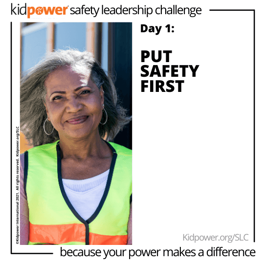 Adult woman crossing guard smiling. Text: Day 1: Put Safety First #KidpowerSLC