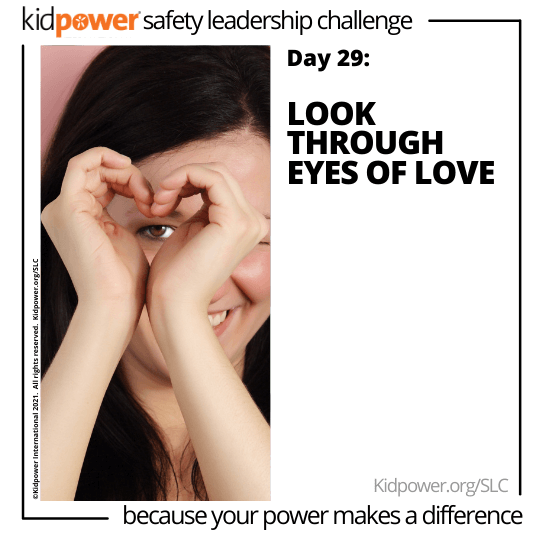 Teen girl making heart with hands over one eye. Text: Day 29: Look Through Eyes of Love #KidpowerSLC