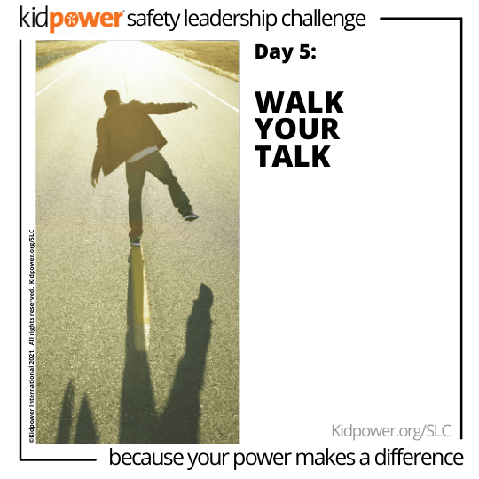 Back of man walking on road median. Text: Day 5: Walk Your Talk #KidpowerSLC